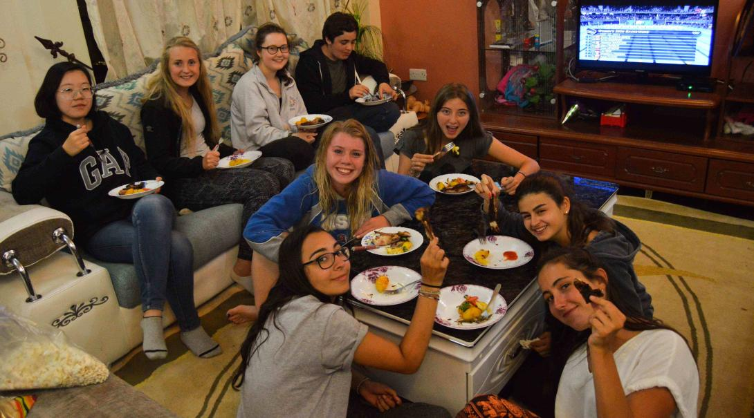 Projects Abroad volunteers enjoy dinner in their host family's living room in Kenya